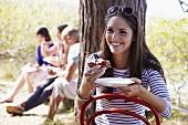 Junge Frau isst Crostini mit Tomaten und Ziegenkäse