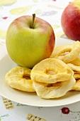 Getrocknete Apfelringe und frische Äpfel