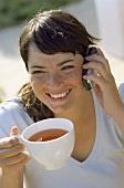 Junge Frau mit Teetasse und Handy