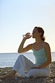 Young woman drinking mineral water by the sea