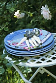 Pile of plates with napkins and cutlery on a garden table