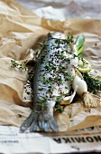 Trout with herbs and spices on greaseproof paper