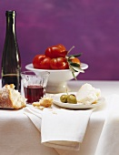 Still life: white bread, Parmesan, olives, red wine & tomatoes