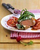 Loin of veal with rocket crust and tomato & radish salad