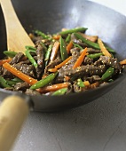 Strips of beef with vegetables and sesame seeds in a wok