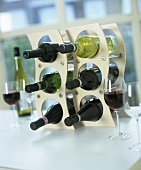 Bottles of red and white wine in wine rack, wine glasses