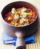 Basil dumplings in tomato and pepper sauce