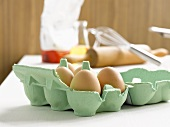 Eggs in egg box, rolling pin, whisk and flour behind