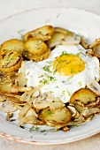 Fried potatoes with fried egg, fennel and mushrooms