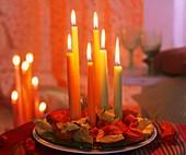 Kerzen auf Glasteller mit Lampionblumen und Herbstlaub