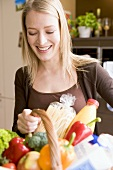 Young woman with fresh products in shopping basket