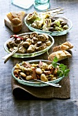 Drei Schälchen mit Tapas (Bohnensalat, Pilze, Artischocken)