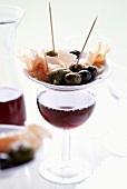Tapas-Teller mit Oliven und Serranoschinken auf Rotweinglas