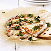 Home-made pizza with anchovies and basil leaves