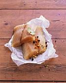 Alaska-Seelachsfilet mit Gewürzen auf Papier