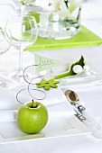 Green apple and place card on white plate