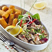 Strips of meat with mustard sauce and potato croquettes