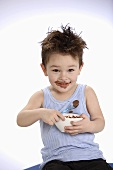 Small boy holding bowl of chocolate pudding