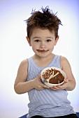 Small boy holding bowl of chocolate pudding towards camera