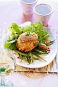 Potato pancake with ham on salad