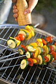 Vegetable skewers being seasoned on barbecue