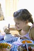 Mädchen isst Honig am Tisch (Bulgarien)