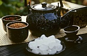 Sugar crystals, various types of tea and teapot
