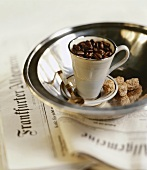 Coffee cup filled with coffee beans in silver bowl on newspaper
