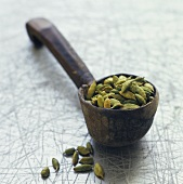 Cardamom pods in wooden spoon