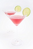 Two Cosmopolitan cocktails with slices of lime