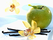 A Granny Smith apple with vanilla pods and orchid