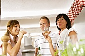 Three young people drinking white wine in kitchen