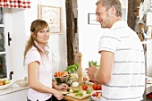 Young couple slicing vegetables in kitchen