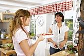 Freundinnen bereiten ein Gemüsegericht in der Küche zu