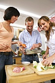 Three young people preparing chicken dish together