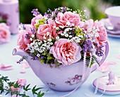 Kleiner Strauss aus rosa Rosen und Schleierkraut in Teekanne