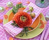 Orangefarbene Ranunkelblüte als Tellerdeko