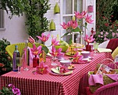 Laid table decorated with lilies in bottles