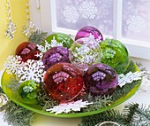 Schale mit durchsichtigen Weihnachtsbaumkugeln und Sternen