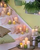 Treppe mit weissen und grünen Kerzen, Tuch und Kissen