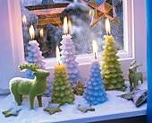 Kerzen in Weihnachtsbaumform, Sterne und Elchfigur am Fenster