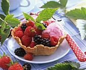 Raspberries and blackberries with ice cream in waffle bowl