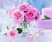 Strauss aus rosa Rosen, daneben Pralinen und Geschenkkartons