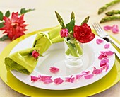 Place-setting decorated with green asparagus and roses