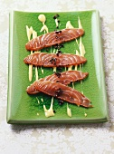 Four slices of salmon marinated in coffee with saffron sauce