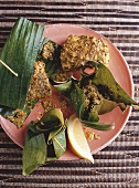 Banana flower in parcel, fish with mustard in banana leaf (India)