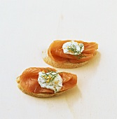 Two open smoked salmon sandwiches with dill cream