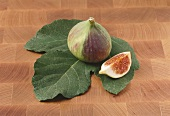 A fig with a piece of fig on a leaf