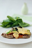 Veal steak with tomato sauce, avocado and melted cheese
