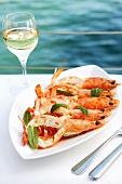 Grilled king prawns on table by sea